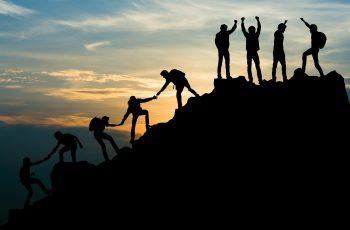 Group of people on peak mountain climbing helping team work , travel trekking success business concept